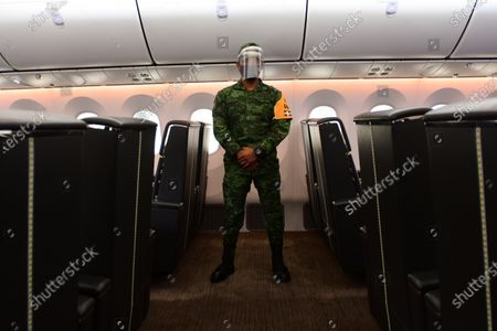 Stock Photo of A soldier guards inside the Mexican presidential plane, a Boeing 787 acquired during the past administration, in the hangar of military base 19 of the Benito Juarez International Airport, in Mexico City, Mexico, 27 July 2020. The Mexican presidential plane was used by Enrique Pena Nieto and his successor, Andres Manuel Lopez Obrador, wants to sell for $130 million.