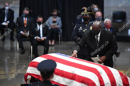 John-Miles Lewis touches the casket of his father, United States Representative John Lewis (Democrat of Georgia), during the memorial service in the Rotunda of the U.S. Capitol in Washington D.C.