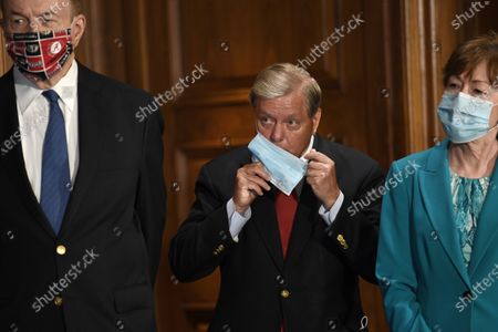 Stock Image of Sen. Richard Shelby, R-Ala., left, Sen. Lindsey Graham, R-S.C., center, and Sen. Susan Collins, R-Maine, right, listen during a news conference on on Capitol Hill in Washington, to highlight the new Republican coronavirus aid package