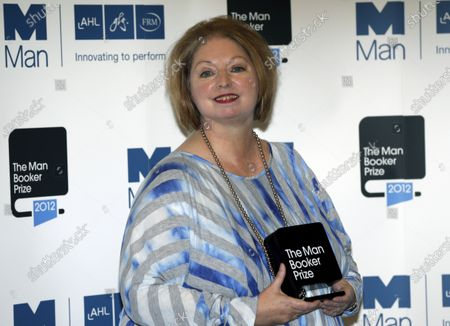 """Hilary Mantel, winner of the Man Booker Prize for Fiction, poses with her prize for the photographers shortly after the award ceremony in central London. Mantel and American author Anne Tyler are among 13 writers on a U.S.-dominated list of contenders for the prestigious Booker Prize for fiction. Mantel was named among competitors for the 50,000 pound ($63,000) literary prize Monday, July 27, 2020, for the """"The Mirror and the Light,"""" the third installment in her trilogy about Tudor power broker Thomas Cromwell"""