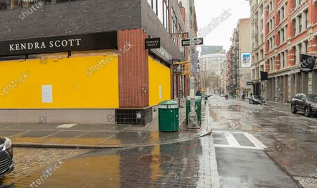 Some high end stores like Kendra Scott on Greene Street boarding up with plywood windows and entrances to prevent looting in Manhattan