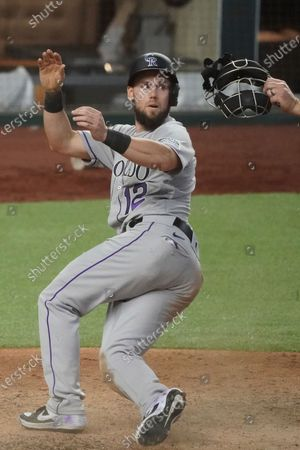 Colorado Rockies pinch runner Chris Owings (12) crosses home plate safely in a baseball game against the Texas Rangers, in Arlington, Texas
