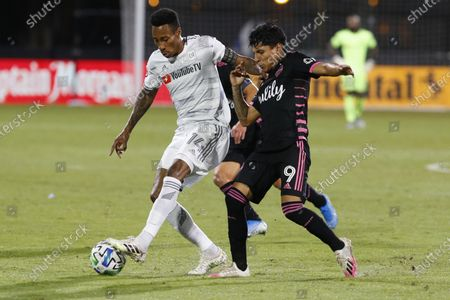 Seattle Sounders forward Raul Ruidiaz (9) and Los Angeles FC midfielder Mark-Anthony Kaye (14) compete for the ball during the first half of an MLS soccer match in Kissimmee, Fla., on