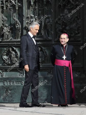 """In this, Italian singer Andrea Bocelli stands next to Archbishop of Milan Mario Delpini prior to performing outside the Duomo cathedral, on Easter Sunday, in Milan, Italy. Italian tenor Andrea Bocelli, who had COVID-19, says the pandemic lockdown in his country made him feel """"humiliated and offended"""" for depriving him of freedom. Bocelli spoke at a panel held on Monday in a Senate conference room, where he was introduced by right-wing opposition leader Matteo Salvini, who has railed against the government's stringent measures aimed at reining in the coronavirus outbreak"""