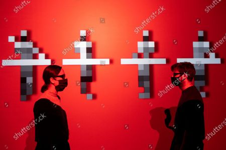 Stock Image of Design Museum staff member pose in front of a Kraftwerk 3d video installation on display at The Design Museum exhibition 'Electronic: From Kraftwerk to The Chemical Brothers'. The exhibition explores the hypnotic world of electronic music and discovers its global impact from underground movements to the mainstream and features appearances from the likes of Jeff Mills, Ellen Allien, Jean-Michel Jarre and more. It will also feature a 3-D experience surrounding electronic pioneers Kraftwerk, with the installation soundtracked by legendary DJ and producer, Laurent Garnier.
