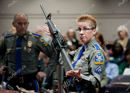 Firearms training unit Detective Barbara J. Mattson, of the Connecticut State Police, holds up a Bushmaster AR-15 rifle, produced by Remington Arms and the same make and model of gun used by Adam Lanza in the Sandy Hook School shooting, for a demonstration during a hearing of a legislative subcommittee reviewing gun laws, at the Legislative Office Building in Hartford, Conn. Remington Arms has filed for Chapter 11 bankruptcy protection, for the second time in a little more than two years, despite a recent surge in gun demand. Remington is currently embroiled in a lawsuit involving the the 2012 Sandy Hook school shooting