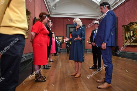 Camilla Duchess of Cornwall (C) flanked by National Gallery Director Gabriele Finaldi (R) and Chair of the Board of Trustees Tony Hall meets staff as she visits the recently reopened National Gallery in London on July 28, 2020.