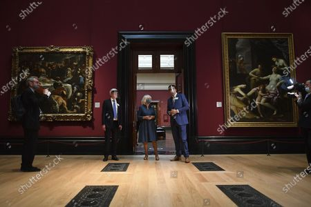 Britain's Camilla, the Duchess of Cornwall, centre, talks to gallery director Gabriele Finaldi, centre right, and chair of the board of trustees Tony Hall, as they walk through the recently reopened National Gallery, meeting members of staff involved in the organisation's Covid-19 response and reopening process, in London