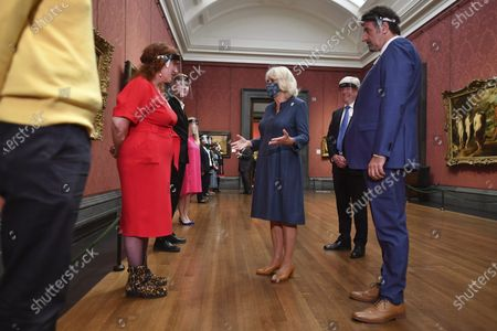 Britain's Camilla, the Duchess of Cornwall, centre, is introduced to staff involved in the organisation's Covid-19 response and reopening process, with gallery director Gabriele Finaldi, right, and chair of the board of trustees, Tony Hall, background right, during a visit to the recently reopened National Gallery, in London