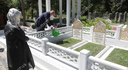 """Turkey's President Recep Tayyip Erdogan and his wife Emine Erdogan visit the graveyards of his parents, in Istanbul, . A top Turkish official said Tuesday that Turkey will suspend research for oil and gas exploration in disputed waters in the Eastern Mediterranean. Erdogan told his aides to """"be constructive and put this on hold for some time,"""" presidential spokesman Ibrahim Kalin told Turkish broadcaster CNN Turk"""