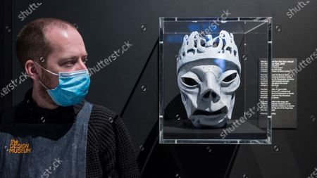 """CITY, UK. A staff member wearing a facemask next to a mask used for the live visual for """"Mad as Hell"""", 2019, by The Chemical Brothers. Preview of """"Electronic: From Kraftwerk to The Chemical Brothers"""" at the Design Museum in Kensington which is reopening after coronavirus lockdown. The new exhibition explores the hypnotic world of electronic music, from its origins to its futuristic dreams. The show runs 31 July 2020 - 14 February 2021 with visitors required to adhere to strict social distancing guidelines."""