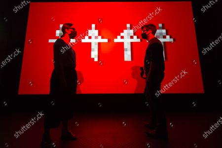 """CITY, UK. Staff members pose in front of the 3D video installation """"12345678"""", 2017, by Kraftwerk. Preview of """"Electronic: From Kraftwerk to The Chemical Brothers"""" at the Design Museum in Kensington which is reopening after coronavirus lockdown. The new exhibition explores the hypnotic world of electronic music, from its origins to its futuristic dreams. The show runs 31 July 2020 - 14 February 2021 with visitors required to adhere to strict social distancing guidelines."""