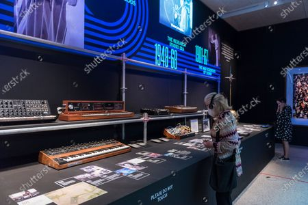 """CITY, UK. A visitor views early synthesisers at the preview of """"Electronic: From Kraftwerk to The Chemical Brothers"""" at the Design Museum in Kensington which is reopening after coronavirus lockdown. The new exhibition explores the hypnotic world of electronic music, from its origins to its futuristic dreams. The show runs 31 July 2020 - 14 February 2021 with visitors required to adhere to strict social distancing guidelines."""