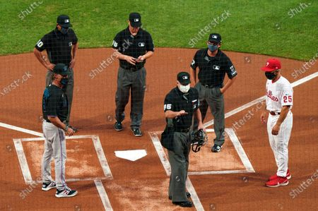Home plate umpire Tim Timmons, center, explains things to Miami Marlins manager Don Mattingly, left, and Philadelphia Phillies manager Joe Girardi, right, with the other umpires looking on prior to a baseball game in Philadelphia. The Miami Marlins' coronavirus outbreak could endanger the Major League Baseball season, Dr. Anthony Fauci said, as the number of their players testing positive rose to 15. The Marlins received positive test results for four additional players Tuesday, July 123, 2020, a person familiar with the situation told The Associated Press. The person declined to be identified because the results had not been publicly released