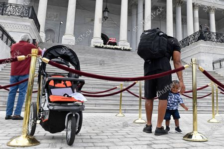 Isaiah Coleman, second from right, of Washington, stands with his one-year-old son Isaiah Coleman, Jr., as they visit the flag-draped casket of the late Rep. John Lewis, D-Ga., as he lies in state at the top of the East steps on Capitol Hill in Washington
