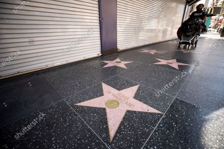 A homeless man pushes a cart past the star of British-US actress Olivia de Havilland on the Walk of Fame in Hollywood, California, USA, 28 July 2020. According to media reports, Olivia de Havilland has died aged 104 in Paris.