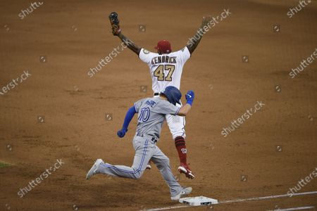Washington Nationals first baseman Howie Kendrick (47) jumps as Toronto Blue Jays' Reese McGuire (10) reaches first during the fifth inning of a baseball game, in Washington. Nationals second baseman Starlin Castro was charged with a throwing error on the play. The Blue Jays won 5-1