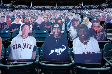Cardboard cutouts of former football players Steve Young, from left, and Jerry Rice sit next to former baseball player Barry Bonds in seats at Oracle Park before a baseball game between the San Francisco Giants and the San Diego Padres in San Francisco