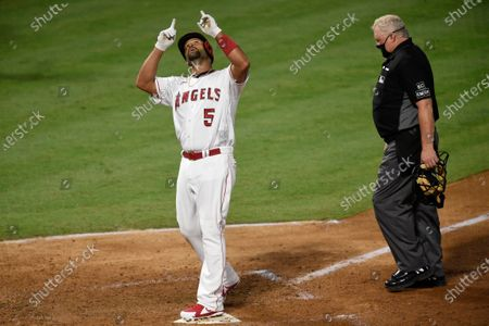 Los Angeles Angels' Albert Pujols points up while crossing home plate next to home plate umpire Bill Miller after a solo home run during the fifth inning of the team's baseball game against the Seattle Mariners in Anaheim, Calif