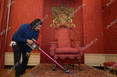 An Historic Royal Palaces conservator vacuums around the throne in the King's Presence Chamber, during a media opportunity at Kensington Palace in London, . Following over four months of closure during lockdown, Kensington Palace will be reopening its doors once more to welcome visitors from Thursday, July 30. To celebrate the re-opening, the famous 'Travolta dress', worn by the late Diana, Princess of Wales, will go on display at the palace for the first time since it was acquired by Historic Royal Palaces at auction in 2019