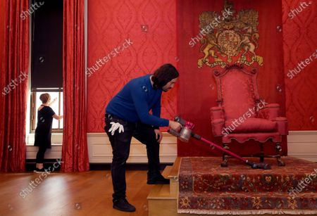 Historic Royal Palaces conservator vacuums around the throne in the King's Presence Chamber, during a media opportunity at Kensington Palace in London, . Following over four months of closure during lockdown, Kensington Palace will be reopening its doors once more to welcome visitors from Thursday, July 30. To celebrate the re-opening, the famous 'Travolta dress', worn by the late Diana, Princess of Wales, will go on display at the palace for the first time since it was acquired by Historic Royal Palaces at auction in 2019