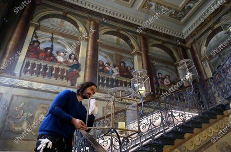 Historic Royal Palaces conservator polishes a candle holder above the King's Staircase, during a media opportunity at Kensington Palace in London, . Following over four months of closure during lockdown, Kensington Palace will be reopening its doors once more to welcome visitors from Thursday, July 30. To celebrate the re-opening, the famous 'Travolta dress', worn by the late Diana, Princess of Wales, will go on display at the palace for the first time since it was acquired by Historic Royal Palaces at auction in 2019