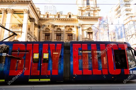 """A tram with """"Billy Elliot"""" displayed in large letters passes in front of the Melbourne Town Hall. As sustained high numbers of new Coronavirus cases are being discovered, Metropolitan Melbourne and the Mitchell Shire remain under Stage 3 restrictions with facemasks being made mandatory on 23 July. 295 new cases were found overnight bringing the states total active case numbers to 4,775."""