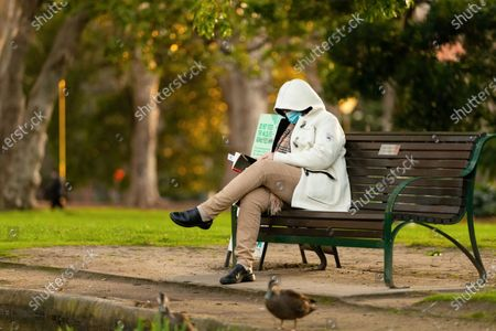 A woman is seen wearing a facemask and reading a book by the pond near The Royal Exhibition Building. As sustained high numbers of new Coronavirus cases are being discovered, Metropolitan Melbourne and the Mitchell Shire remain under Stage 3 restrictions with facemasks being made mandatory on 23 July. 295 new cases were found overnight bringing the states total active case numbers to 4,775.