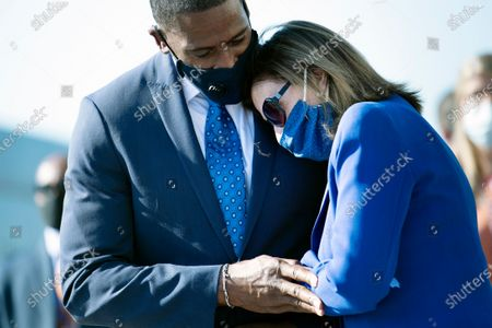 Michael Collins, Representative Lewis's long time chief of staff, and Speaker of the House Nancy Pelosi of Calif., embrace after the flag-draped casket of the late Rep. John Lewis, D-Ga., was carried away by a joint services military honor guard from Capitol Hill, in Washington