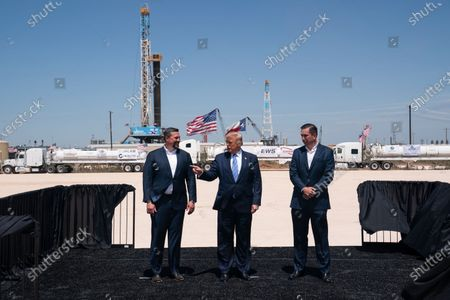 President Donald Trump stands with Double Eagle Energy co-CEOs Cody Campbell, left, and John Sellers, right, as he arrives at the Double Eagle Energy Oil Rig, in Midland, Texas