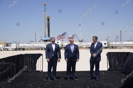 Stock Picture of President Donald Trump stands with Double Eagle Energy co-CEOs Cody Campbell, left, and John Sellers, right at the Double Eagle Energy Oil Rig, in Midland, Texas