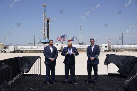 President Donald Trump adjusts his jacket as he stands with Double Eagle Energy co-CEOs Cody Campbell, left, and John Sellers, right at the Double Eagle Energy Oil Rig, in Midland, Texas