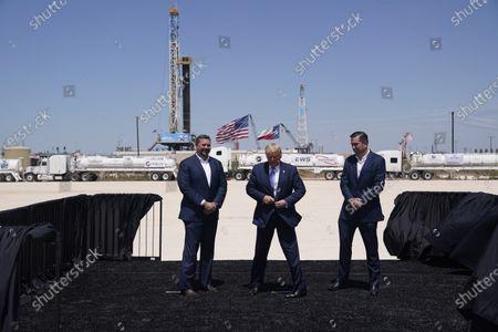 Stock Image of President Donald Trump adjusts his jacket as he stands with Double Eagle Energy co-CEOs Cody Campbell, left, and John Sellers, right at the Double Eagle Energy Oil Rig, in Midland, Texas