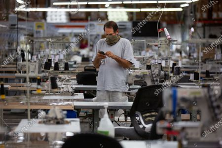 Stock Picture of LA Apparel, CEO, Dov Charney, 51, of Los Angeles checks his phone on the sewing floor at LA Apparel during an employee health and safety training session on Wednesday, July 15, 2020 in Los Angeles, CA. (Jason Armond / Los Angeles Times)