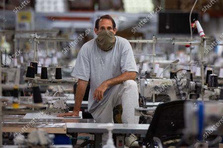 Stock Photo of LA Apparel, CEO, Dov Charney, 51, of Los Angeles poses for a portrait on the sewing floor at LA Apparel during an employee health and safety training session on Wednesday, July 15, 2020 in Los Angeles, CA. (Jason Armond / Los Angeles Times)