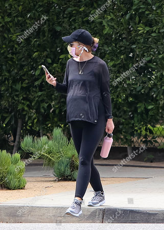 Katherine Schwarzenegger talks on the phone while going for a walk