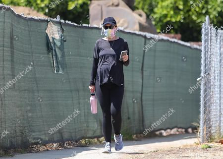Stock Photo of Katherine Schwarzenegger talks on the phone while going for a walk