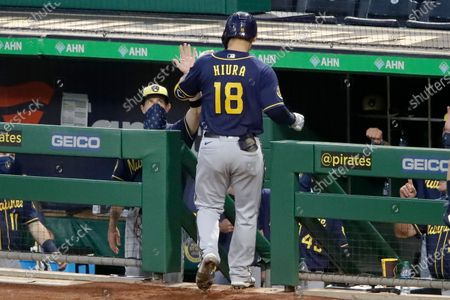 Milwaukee Brewers manager Craig Counsell, left center, greets Keston Hiura (18) as he returns to the dugout after hitting a solo home run off Pittsburgh Pirates starting pitcher Joe Musgrove during the sixth inning of a baseball game in Pittsburgh