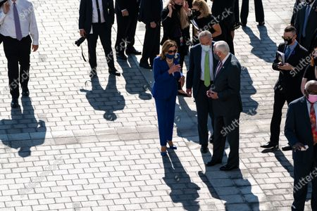 Speaker of the United States House of Representatives Nancy Pelosi (Democrat of California) speaks with US Senate Minority Leader Chuck Schumer (Democrat of New York) and US House Majority Leader Steny Hoyer (Democrat of Maryland) after the casket of United States Representative John Lewis (Democrat of Georgia) was carried down the Capitol steps in Washington, DC,.