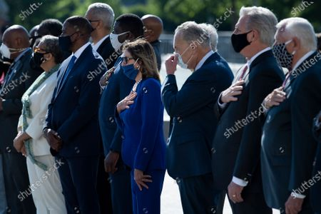 Speaker of the United States House of Representatives Nancy Pelosi (Democrat of California), US Senate Minority Leader Chuck Schumer (Democrat of New York), US House Minority Leader Kevin McCarthy (Republican of California), US House Majority Leader Steny Hoyer (Democrat of Maryland) and other lawmakers watch as a casket with the remains of US Representative John Lewis (Democrat of Georgia) is carried from the US Capitol building, in Washington, DC.