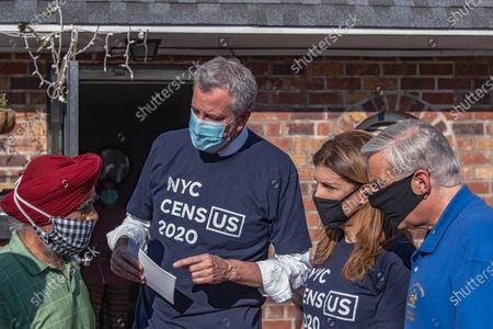 Stock Picture of Mayor Bill de Blasio, NYC Census 2020 Director Julie Menin and Assembly Member David Weprin talk to Mr. Singh in Queens borough, New York City. Mayor Bill de Blasio and NYC Census 2020 Director Julie Menin go door-knocking to encourage New Yorkers to complete the census in South Richmond Hill, Queens.
