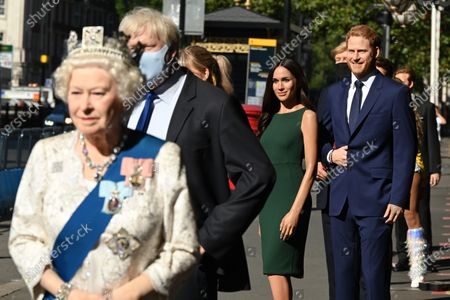 (L-R) The Queen, Meghan Duchess of Sussex and Prince Harry at Madame Tussauds re-opening in London