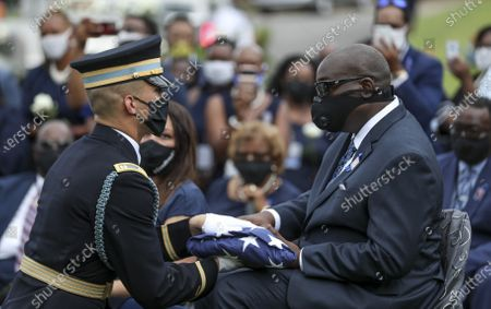 The honor guard lpresents the folded American flag whcih had covered the casket to John-Miles Lewis, John Lewis' son, during the burial at Southview Cemetery following  the Celebration of Life Service for civil rights leader and Democratic Representative from Georgia John Lewis at Ebenezer Baptist Church in Atlanta, Georgia, USA, 30 July 2020. Lewis died at age 80 on 17 July 2020 after being diagnosed with pancreatic cancer in December 2019. John Lewis was the youngest leader in the March on Washington in 1963.