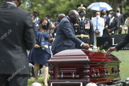 John-Miles Lewis places flowers on his father's casket during the burial at Southview Cemetery following  the Celebration of Life Service for civil rights leader and Democratic Representative from Georgia John Lewis at Ebenezer Baptist Church in Atlanta, Georgia, USA, 30 July 2020. Lewis died at age 80 on 17 July 2020 after being diagnosed with pancreatic cancer in December 2019. John Lewis was the youngest leader in the March on Washington in 1963.