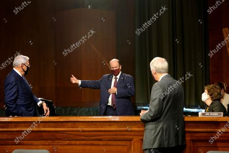 Sen. Chris Coons, D-Del, center, speaks to Sen. Robert Menendez, D-N.J., Rob Portman, R-Ohio, and Jeanne Shaheen, D-N.H., during a break in a Senate Foreign Relations committee hearing on the State Department's 2021 budget on Capitol Hill, in Washington