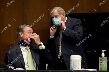 Sen. David Perdue, R-Ga., speaks to Sen. Lindsey Graham, R-S.C., during a Senate Foreign Relations committee hearing on the State Department's 2021 budget on Capitol Hill, in Washington