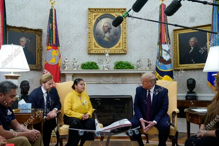 President Donald Trump meets with the family of slain Army Spc. Vanessa Guillen in the Oval Office of the White House, in Washington. Vanessa's mother Gloria Guillen, third from left, and Vanessa's father Rogelio Guillen, left, listen