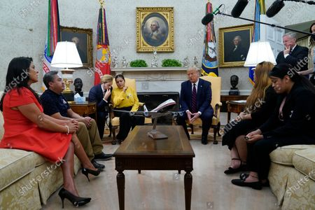 President Donald Trump speaks as he meets with the family of slain Army Spc. Vanessa Guillen in the Oval Office of the White House, in Washington. Seated from left, family attorney Natalie Khawam, Vanessa's father Rogelio Guillen, Vanessa's mother Gloria Guillen, Trump, Vanessa's sister Mayra Guillen and Vanessa's sister Lupe Guillen. White House Chief of Staff Mark Meadows stands at top right