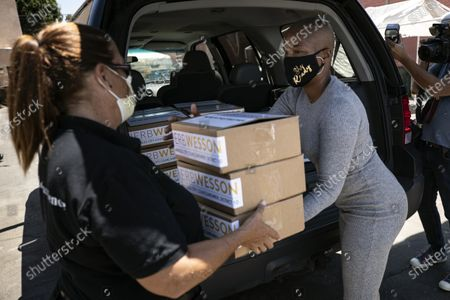 US actress Tiffany Haddish (R) helps distribute computers to students in foster care during a drive-thru giveaway amid the coronavirus pandemic in Los Angeles, California, USA, 30 July 2020. The computers are donated by Wesson's 'OurCycleLA' project, a digital inclusion program designed to bridge the digital divide in low-income households in Los Angeles and other marginalized communities.