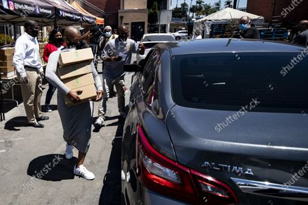 US actress Tiffany Haddish distributes computers to students in foster care during a drive-thru giveaway amid the coronavirus pandemic in Los Angeles, California, USA, 30 July 2020. The computers are donated by Wesson's 'OurCycleLA' project, a digital inclusion program designed to bridge the digital divide in low-income households in Los Angeles and other marginalized communities.
